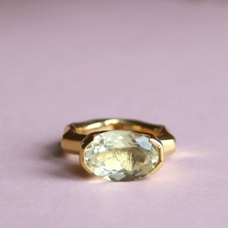 a ring lays on a pink background sustainable gold boasting a beautiful stone
