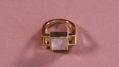 a ring lays on a pink background sustainable gold jewellery boasting a beautiful stone