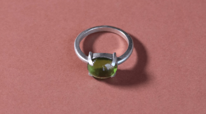 a green stone on a silver band lays on a pink background