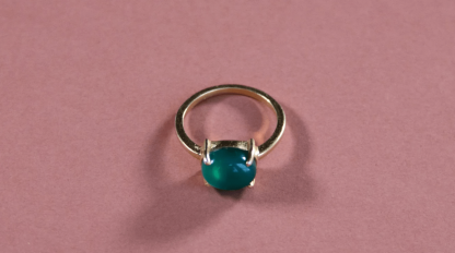 a blue stone on a gold band lays on a pink background
