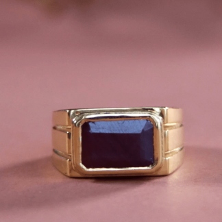 a gold ring with a stunning stone stands alone on a table