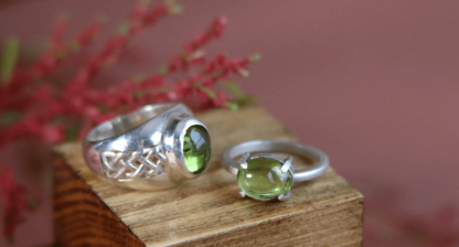 a silver ring with a green stone stood next to a thinner ring with the same green gem