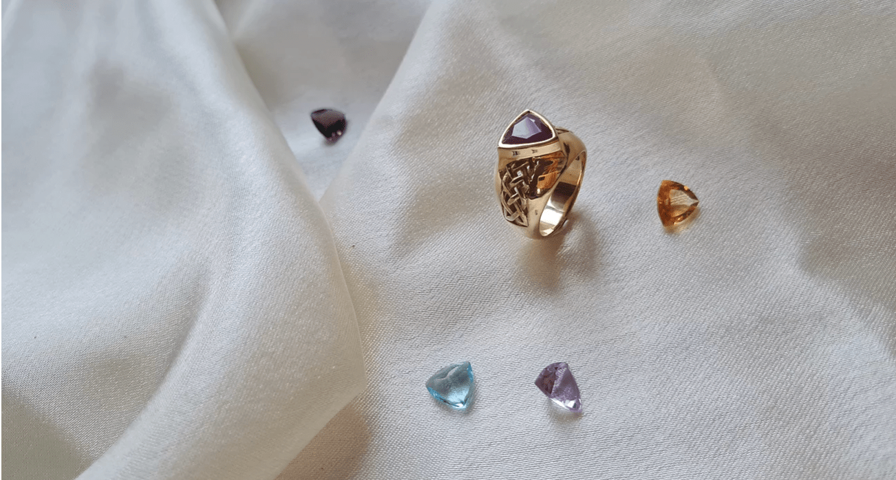 a gold ring with a stunning stone stands aside stunning stone options on a table